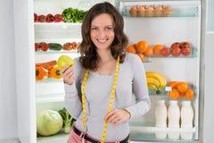 Mulher com fita e Apple de medição perto do refrigerador Imagens de Stock