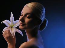 Mulher com a flor do lírio tonificada no azul Fotos de Stock