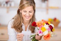 Mulher com flores e cartão Fotografia de Stock Royalty Free