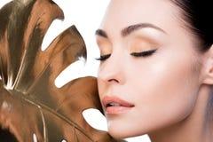 Mulher com a folha dourada grande perto da cara Fotografia de Stock