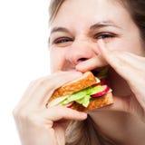 Mulher com fome que come o sanduíche Fotografia de Stock