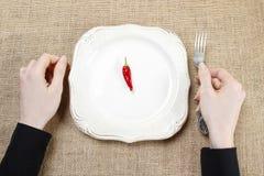 Mulher com fome que come pimentas de pimentão encarnados Símbolo da adaptação a Foto de Stock Royalty Free