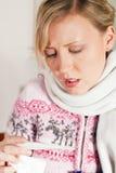 Mulher com a gripe que toma sua temperatura Fotografia de Stock