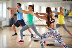 A mulher com grupo de exercitadores expande a borracha resistente fotografia de stock