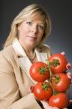 Mulher com grupo de tomates maduros frescos Imagem de Stock