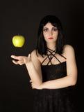A mulher com Halloween compo a maçã verde sthrowing Fotos de Stock Royalty Free