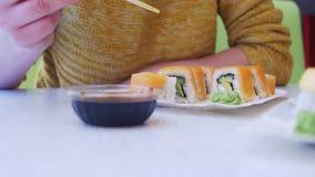 Mulher com hashis que come o sushi de uma placa em um restaurante japonês Tiro da zorra filme