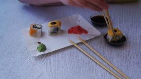 Mulher com hashis que come o sushi de uma placa em um restaurante japonês Tiro da zorra vídeos de arquivo