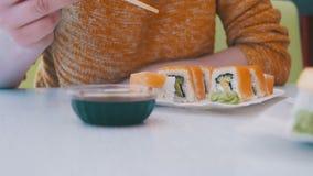 Mulher com hashis que come o sushi de uma placa em um restaurante japonês Tiro da zorra video estoque