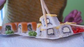 A mulher com hashis toma o sushi de uma placa em um restaurante japonês filme