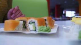 A mulher com hashis toma o sushi de uma placa em um restaurante japonês Tiro da zorra video estoque