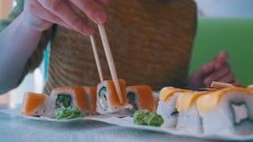 A mulher com hashis toma o sushi de uma placa em um restaurante japonês Tiro da zorra vídeos de arquivo