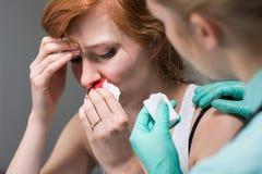 Mulher com hemorragia nasal e enfermeira Foto de Stock Royalty Free