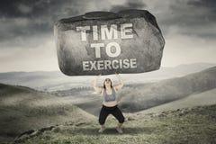 Mulher com hora de exercitar a palavra na pedra Imagem de Stock Royalty Free