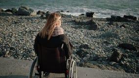 A mulher com inabilidades está sentando-se no transporte inválido e está olhando-se no mar vídeos de arquivo
