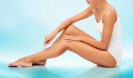 Mulher com a lâmina de segurança que barbeia os pés Fotografia de Stock Royalty Free