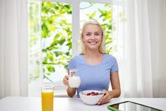 Mulher com leite e flocos de milho que come o café da manhã Foto de Stock