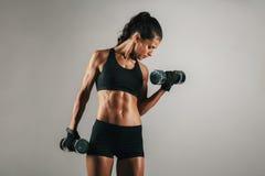 Mulher com levantar peso tonificado do corpo muscular Fotografia de Stock Royalty Free