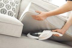 Mulher com limpeza handheld do vácuo no sofá imagens de stock