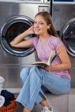 Mulher com livro que escuta a música na lavanderia fotos de stock