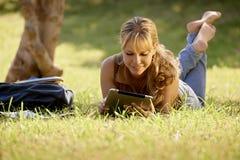 A mulher com livros e o ipad que estudam para a faculdade testam imagens de stock