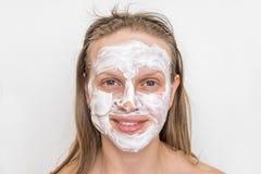 Mulher com máscara de creme branca natural em sua cara imagens de stock