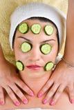 Mulher com a máscara do pepino que começ a massagem da garganta imagens de stock