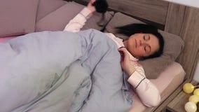 A mulher com máscara do sono da venda acorda na manhã video estoque