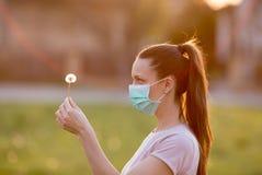 Mulher com máscara e dente-de-leão no parque fotografia de stock royalty free