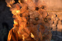 Mulher com a máscara Venetian decorada com folha de ouro e o pano alaranjado, fundo de pedra Fotografia de Stock Royalty Free