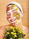 Mulher com máscaras do facial da argila. imagem de stock