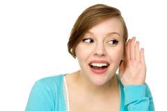 Mulher com mão à orelha que escuta Fotos de Stock