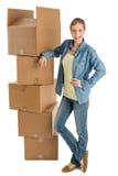 Mulher com mão no quadril que está por caixas de cartão empilhadas imagem de stock royalty free