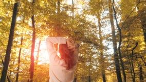 Mulher com mãos levantadas acima na floresta do outono Imagens de Stock