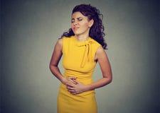 A mulher com mãos no estômago que tem dores más causa dor fotos de stock