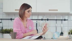 Mulher com música de fala ou de escuta dos fones de ouvido usando o smartphone filme