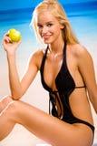 Mulher com a maçã na praia fotos de stock royalty free