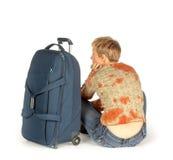 Mulher com a mala de viagem que senta-se na terra Fotos de Stock
