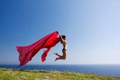 Mulher com material e natureza vermelhos Imagens de Stock
