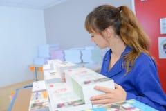 Mulher com material impresso das pilhas imagens de stock