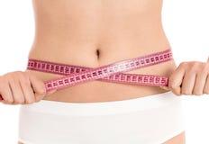 Mulher com medida de fita em torno de sua cintura Foto de Stock