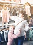 A mulher com a menina demonstra compras novas foto de stock