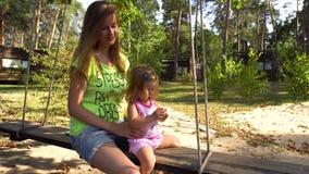 Mulher com a menina na balancê de madeira sob a árvore vídeos de arquivo