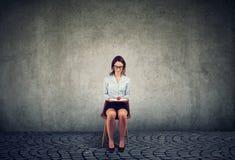 Mulher com o único tomate que senta-se na cadeira imagens de stock royalty free