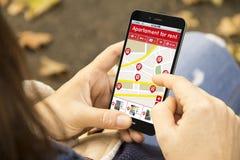 Mulher com o apartamento para o telefone do app da busca do aluguel no parque Imagem de Stock Royalty Free
