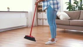 Mulher com o assoalho da limpeza de escova da vassoura da lavagem filme