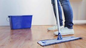 Mulher com o assoalho da limpeza do espanador em casa video estoque