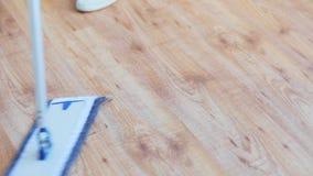 Mulher com o assoalho da limpeza do espanador em casa