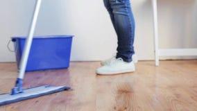 Mulher com o assoalho da limpeza do espanador em casa vídeos de arquivo