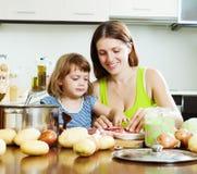Mulher com o bebê que cozinha com carne e vegetais Fotografia de Stock Royalty Free